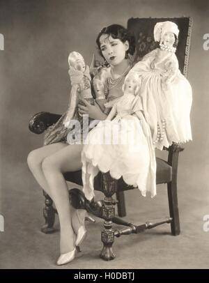 Woman sitting with four dolls - Stock Image