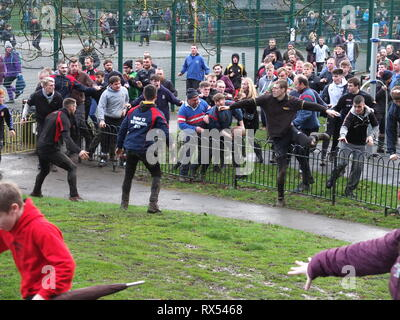 Ashbourne Shrovetide Football 2019. Players scramble to follow the ball as play enters a children's playground during the Ash Wednesday game. - Stock Image