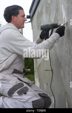 A builder, painter and decorator using a heat gun working on the wall of a house. - Stock Image