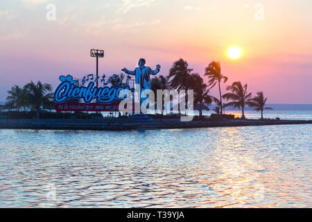 """A Figure of Cuban Man and Welcome sign that reads """"Cienfuegos is the City I like the Most"""" against the Sunset Sky in City of Cienfuegos, Cuba - Stock Image"""