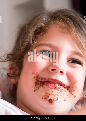 Cute messy with chocolate caucasian girl smiling - Stock Image