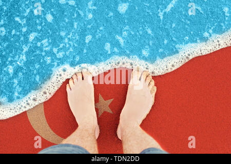 Feet on the sunny sandy beach with flag Turkey. Top View on surf. - Stock Image