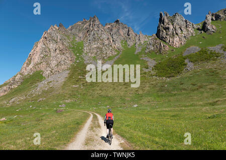 Female cyclist riding from Bleik to Andenes, Vesteralen, Andoya, Norway. - Stock Image