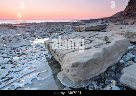 Sunset over the rocky shoreline of Dunraven Bay, Southerdown in South Wales - Stock Image