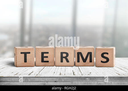 Terms sign in a bright office on a wooden desk with windows in the background - Stock Image