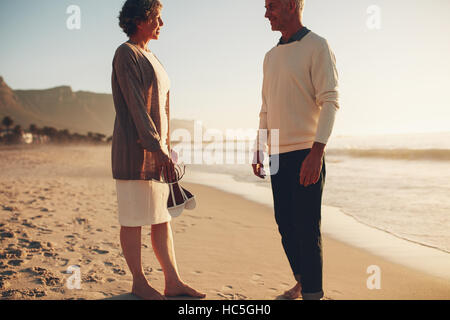 Outdoors shot of happy mature couple standing together on the beach and talking. Senior man and senior woman on - Stock Image