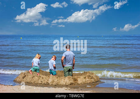 Father with little son and daughter in sand castle on the beach watching the tide coming in along the North Sea coast - Stock Image