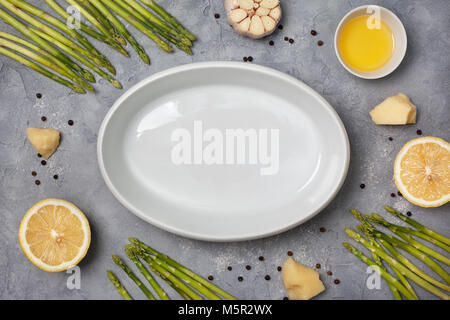 Ingredients for baking: fresh green asparagus, garlic, olive oil, parmesan cheese, lemon on a gray stone background. - Stock Image