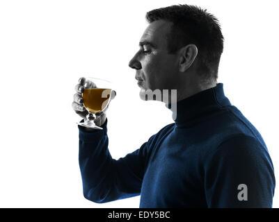 one  man drinking orange juice portrait in silhouette studio isolated on white background - Stock Image