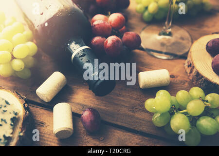red wine bottle with grapes on old wooden background - Stock Image