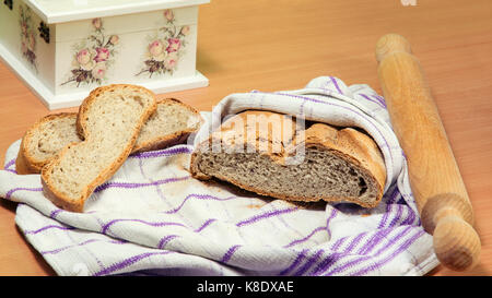 Homemade bread wrapped in kitchen cloth, two bread slices next to it, and a rolling pin. Partially visible, gorgeous - Stock Image