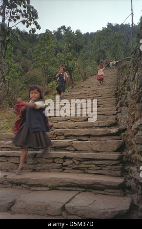 Primary School children running home down stone staircase from school in the afternoon on Annapurna circuit Nepal - Stock Image