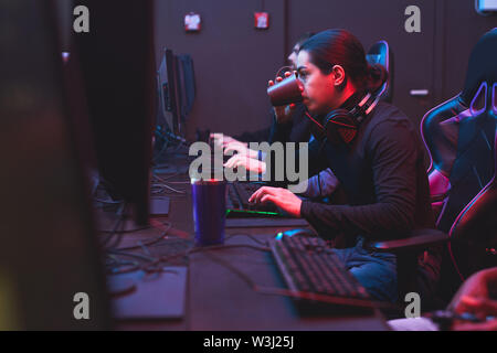 Experienced young man with ponytail sitting at table and drinking tea while using computer and working on web project - Stock Image