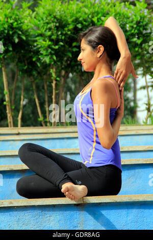 Young Indian woman performing gomukhasana - Stock Image