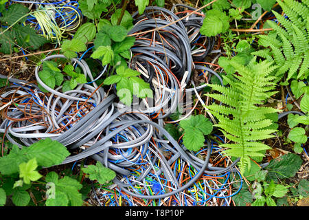 Fly tipped litter, plastic insulation stripped from electric wire and cable dumped in countryside - Stock Image