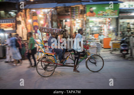 A bicycle rickshaw driver taking a customer down the street on a early evening in New Delhi, India - Stock Image
