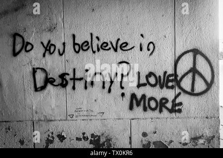 The words 'Do you believe in Destiny?  Love More' spray painted on a white wall. - Stock Image