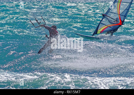 Kiteboarder vs windsurfer  in mediterranean sea during a windy day - Stock Image