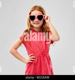 smiling red haired girl in heart shaped sunglasses - Stock Image