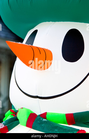 Close-up of an inflatable snowman's face with big smile and orange carrot nose - Stock Image
