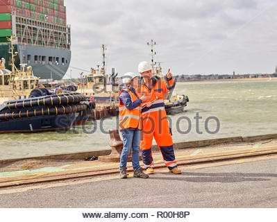 Docks workers manager supervisor standing infront of cargo ship coming into port - Stock Image