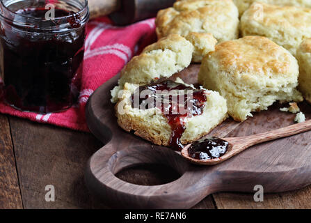 Buttermilk southern biscuits or scones served with homemade fruit preserves. Top view. - Stock Image
