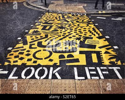 Bright yellow paint is used on a road junction to alert pedestrians as to which way they should be watching in order to be street safe. - Stock Image