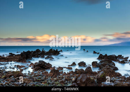 Seascape coastline of west Tenerife at dawn made using long exposure photography with nuetral density filters to create silky water and movement in th - Stock Image
