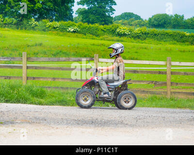 Young boy wearing a safety helmet riding a small Quad Bike on a farm road. - Stock Image