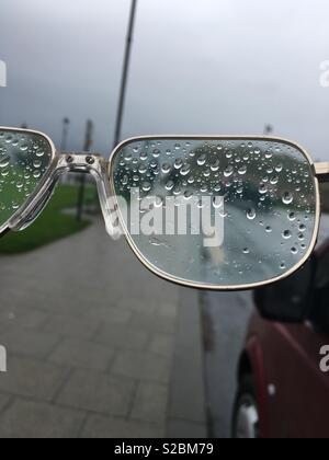 A wet day and rain covers a pair of spectacles making it hard to see. - Stock Image