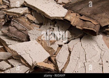 Pieces of broken stucco caused by water damage - Stock Image