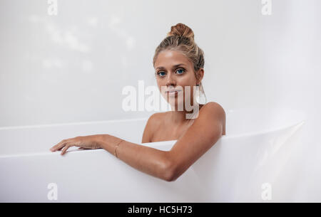 Portrait of young female sitting in bathtub. Female relaxing in bathtub and looking at camera. - Stock Image