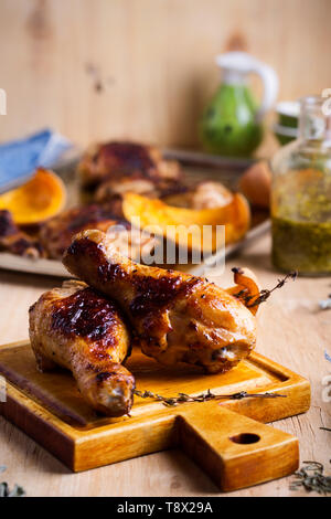 Baked chicken legs with butternut squash and thyme herb on rustic wooden table served with pesto sauce, selective focus - Stock Image