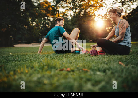 Happy fit young couple exercising in park. Relaxing after physical training session. - Stock Image