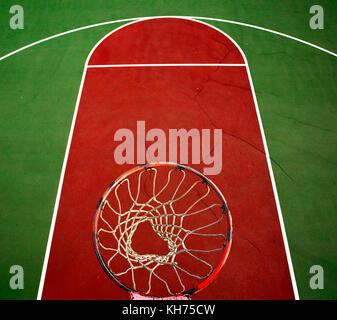 Pole aerial image of an outdoor basketball court. Includes rim, mesh, red key, white lines and green surface. - Stock Image