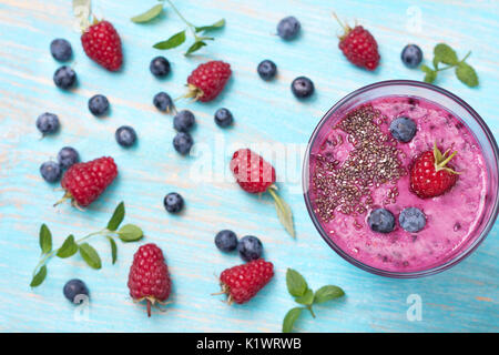 Smoothies with blueberries and raspberries, chia seeds in a glass cup. view from above - Stock Image