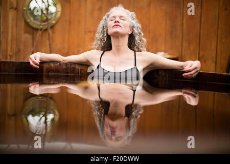 Mature woman meditating with eyes closed in hot tub at eco retreat - Stock Image