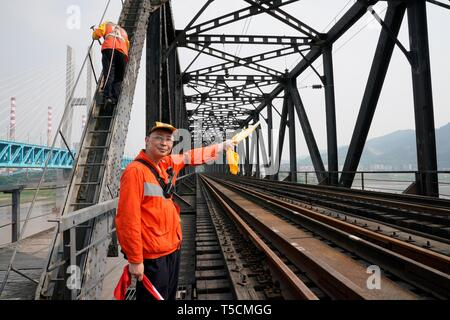 (190423) -- CHONGQING, April 23, 2019 (Xinhua) -- Workers are seen on the previous Baishatuo Yangtze River railway bridge in Jiangjin of southwest China's Chongqing Municipality, April 23, 2019. The previous Baishatuo Yangtze River railway bridge, completed in 1959, will stop service after April 24. All trains will run on the new double decker steel truss cable stay railway bridge after that day. The new bridge has 4 tracks on the upper deck for passenger trains with a designed speed of 200 kilometers per hour and 2 tracks on the lower deck for cargo trains with the designed speed of 120 kilom - Stock Image