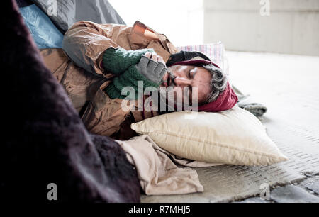 A homeless beggar man lying on the ground outdoors in city asking for money donation, warming up hands. - Stock Image
