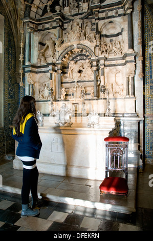 A female visitor to the Palácio da Pena standing in front of the palace chapel's 16th-century alabaster and marble retable.  - Stock Image