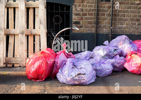 Bags of commercial rubbish and recycling left out for collection - Stock Image