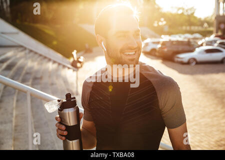 Image of a handsome young strong sports man posing outdoors at the nature park location drinking water. - Stock Image