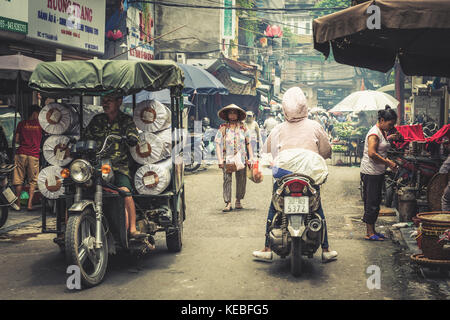 Locals on foot and mopeds in a street in Hanoi's Old Quarter - Stock Image