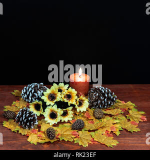 Silk maple leaves, beautiful bouquet of sunflowers, frosted pinecones and orange candle on tabletop with dark background. - Stock Image