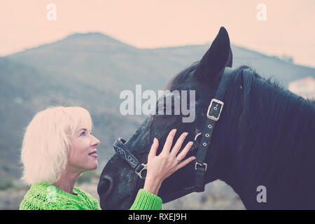Blonde hair happy woman look and hug with care and sweetness her best friend black horse in the outdoor leisure activity - together and friendship con - Stock Image