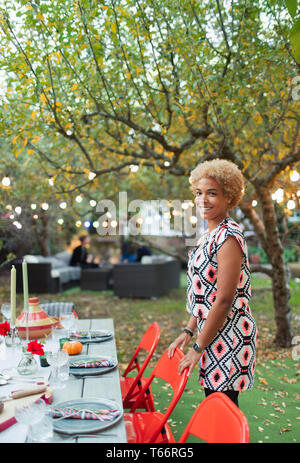Portrait happy woman hosting dinner garden party - Stock Image