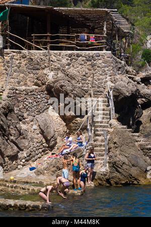 People enjoy water and sunshine beneath Ca's Patro March restaurant in Cala Deia, Mallorca, Spain. - Stock Image