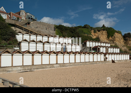 Three rows of white doored beach huts in Swanage against the cliffs with one door opened and blue curtains on view. - Stock Image