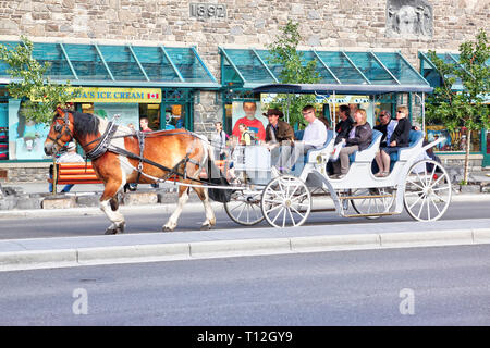 BANFF, CANADA - JULY 3, 2011: Tourists on a horse drawn carriage ride through Banff Avenue in the Canadian Rockies of Alberta. The townsite is a major - Stock Image