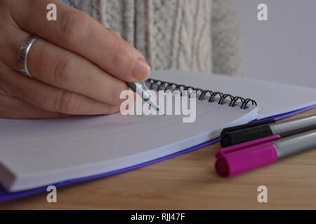 woman writing in a spiral bound notebook, pen in hand, poised over a blank page - Stock Image